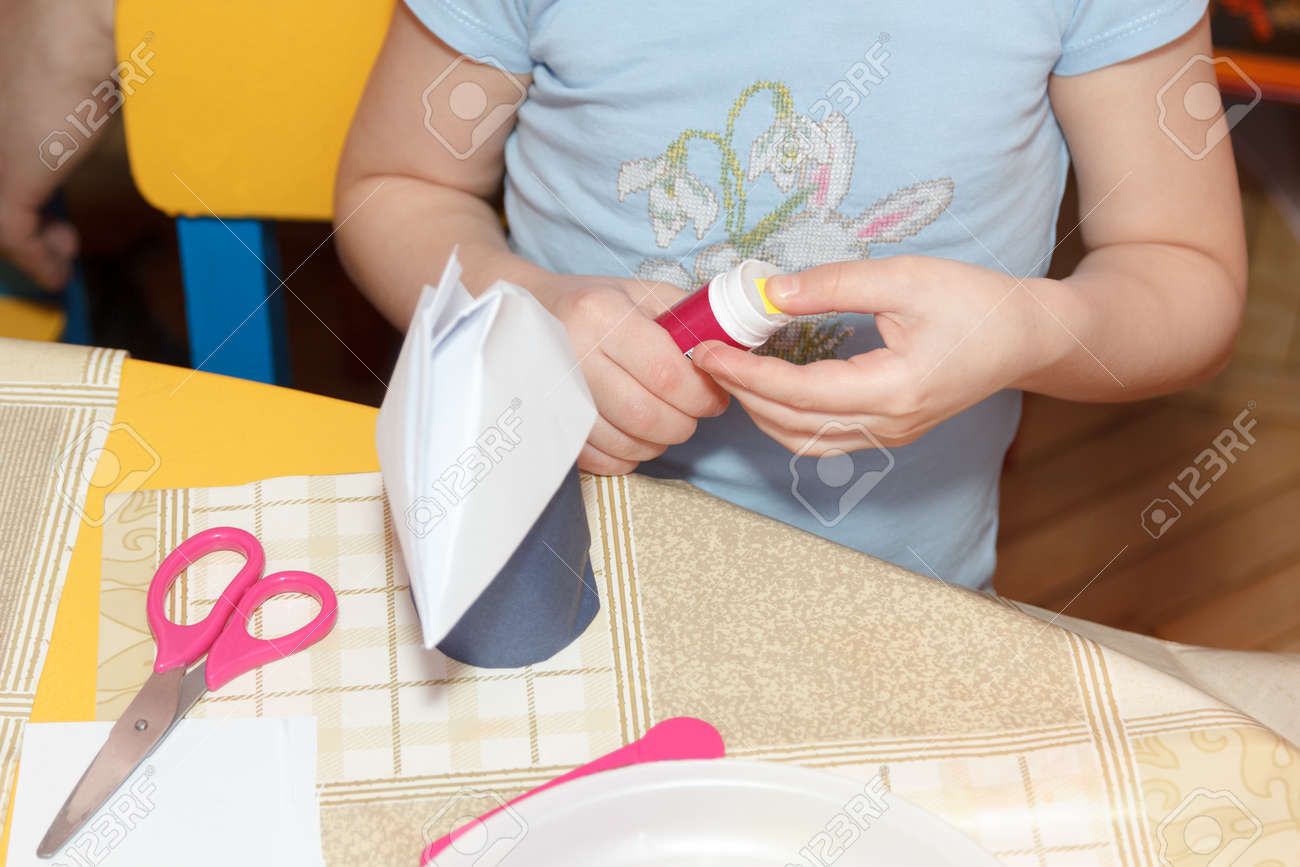 Small Child Hands Glue Paper Crafts At A School Desk Stock Photo