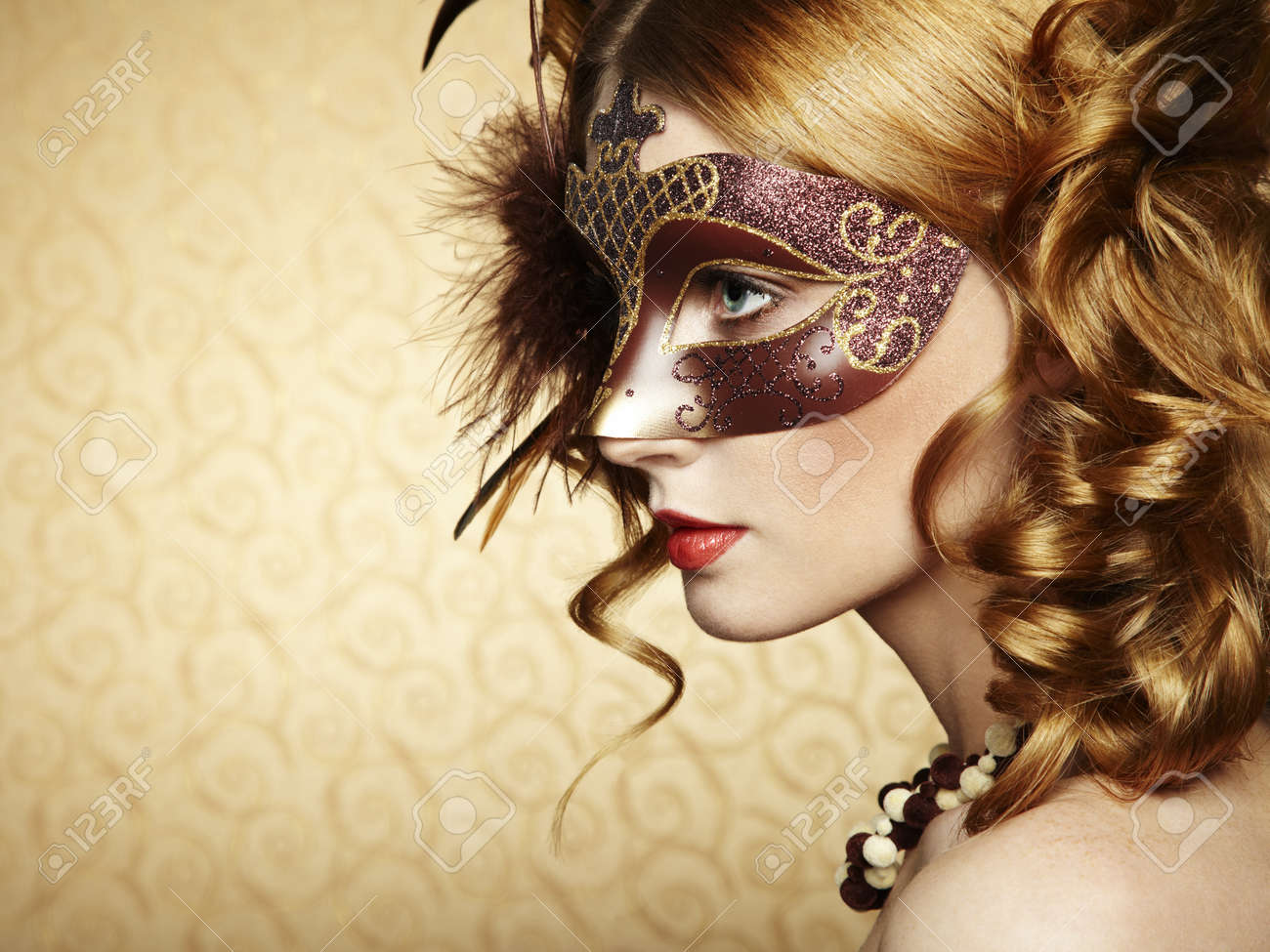 Beautiful young woman in brown mysterious venetian mask. Stock Photo - 16548763