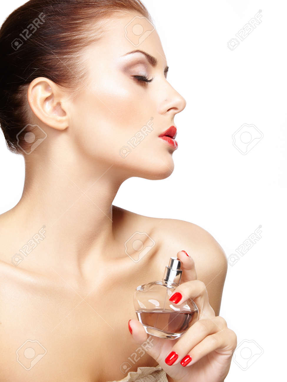 Young woman applying perfume on herself isolated on white background. Fashion photo Stock Photo - 22108187