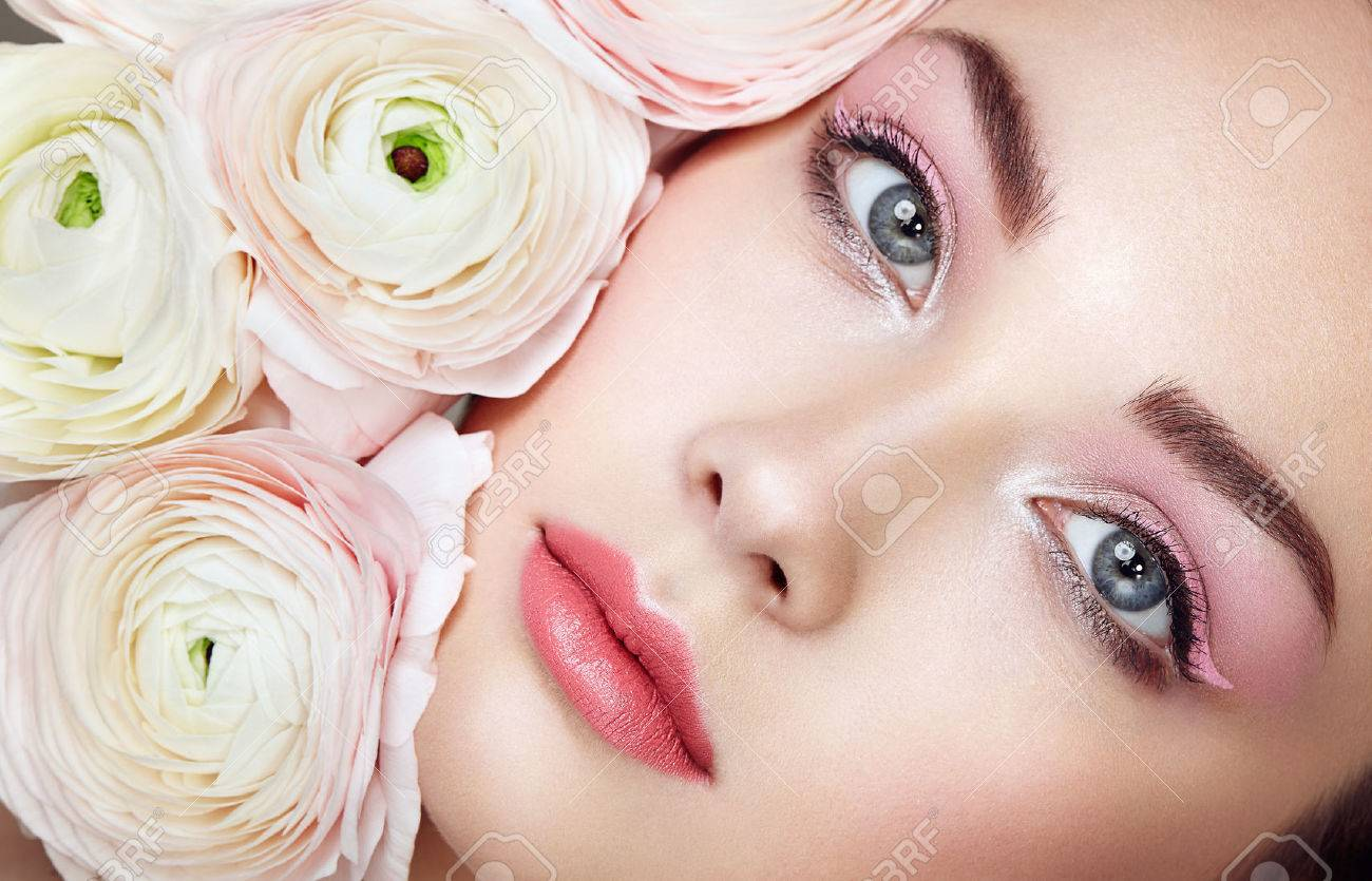 Portrait of beautiful young woman with flowers. Brunette woman with luxury makeup. Perfect skin. Eyelashes. Cosmetic eyeshadow - 56685944