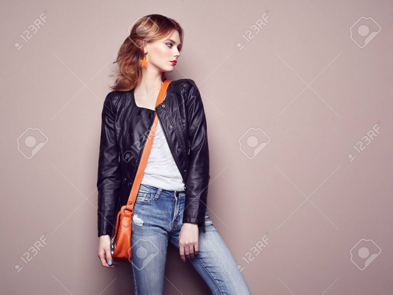 Fashion portrait of beautiful young woman with red hair. Girl in blouse and jeans. Jewelry and hairstyle. Girl with handbag - 58519885