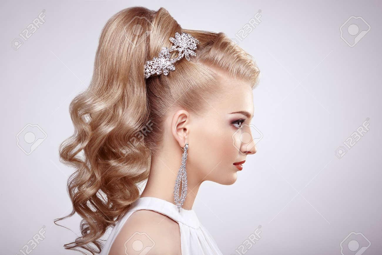 fa3d77e78499 Archivio Fotografico - Moda ritratto di giovane donna bellissima con  gioielli e acconciatura elegante. Ragazza bionda con lunghi capelli  ondulati.