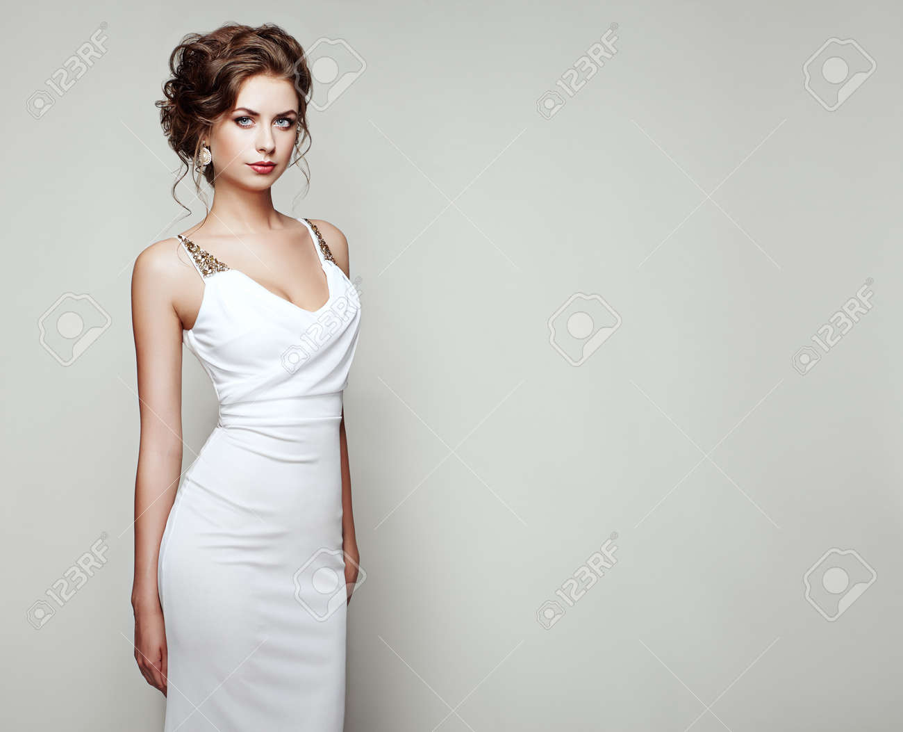 Fashion portrait of beautiful woman in elegant white dress. Girl with elegant hairstyle and jewelry - 64431543