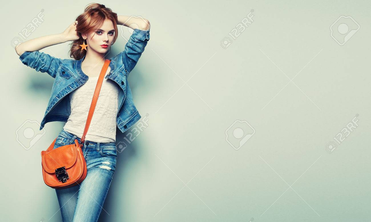 Fashion portrait of beautiful young woman with red hair. Girl in blouse and jeans. Jewelry and hairstyle. Girl with handbag - 65288410