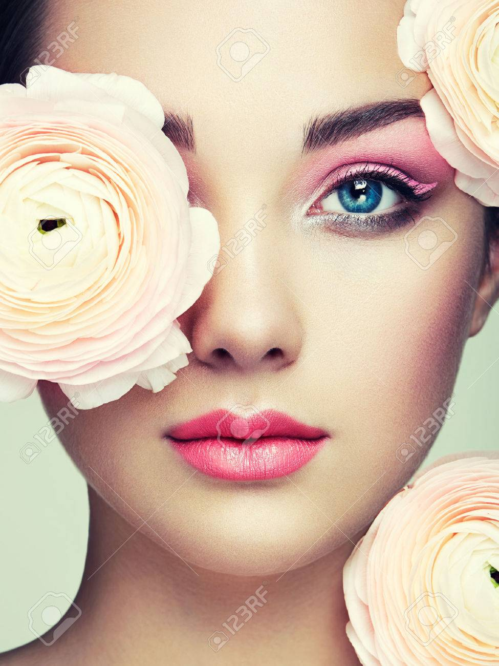 Portrait of beautiful young woman with flowers. Brunette woman with luxury makeup. Perfect skin. Eyelashes. Cosmetic eyeshadow - 65173856