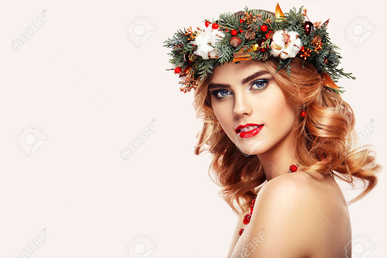Portrait of beautiful young woman with Christmas wreath. Beautiful New Year and Christmas tree holiday hairstyle and makeup. Beauty girl portrait isolated on white background. Colorful makeup and hair - 68058230