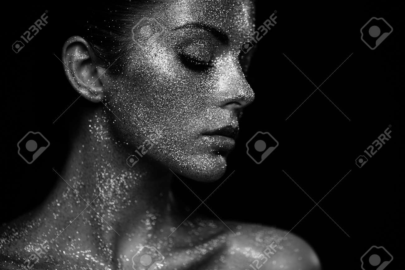 Portrait of beautiful woman with sparkles on her face. Girl with art make up in color light. Fashion model with colorful make-up. Black and White - 68736011