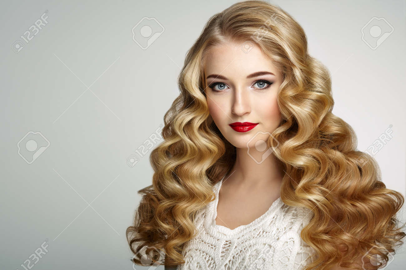 Beautiful girl with long wavy and shiny hair . Blonde woman with curly hairstyle. Perfect make-up. Fashion photo - 69543017