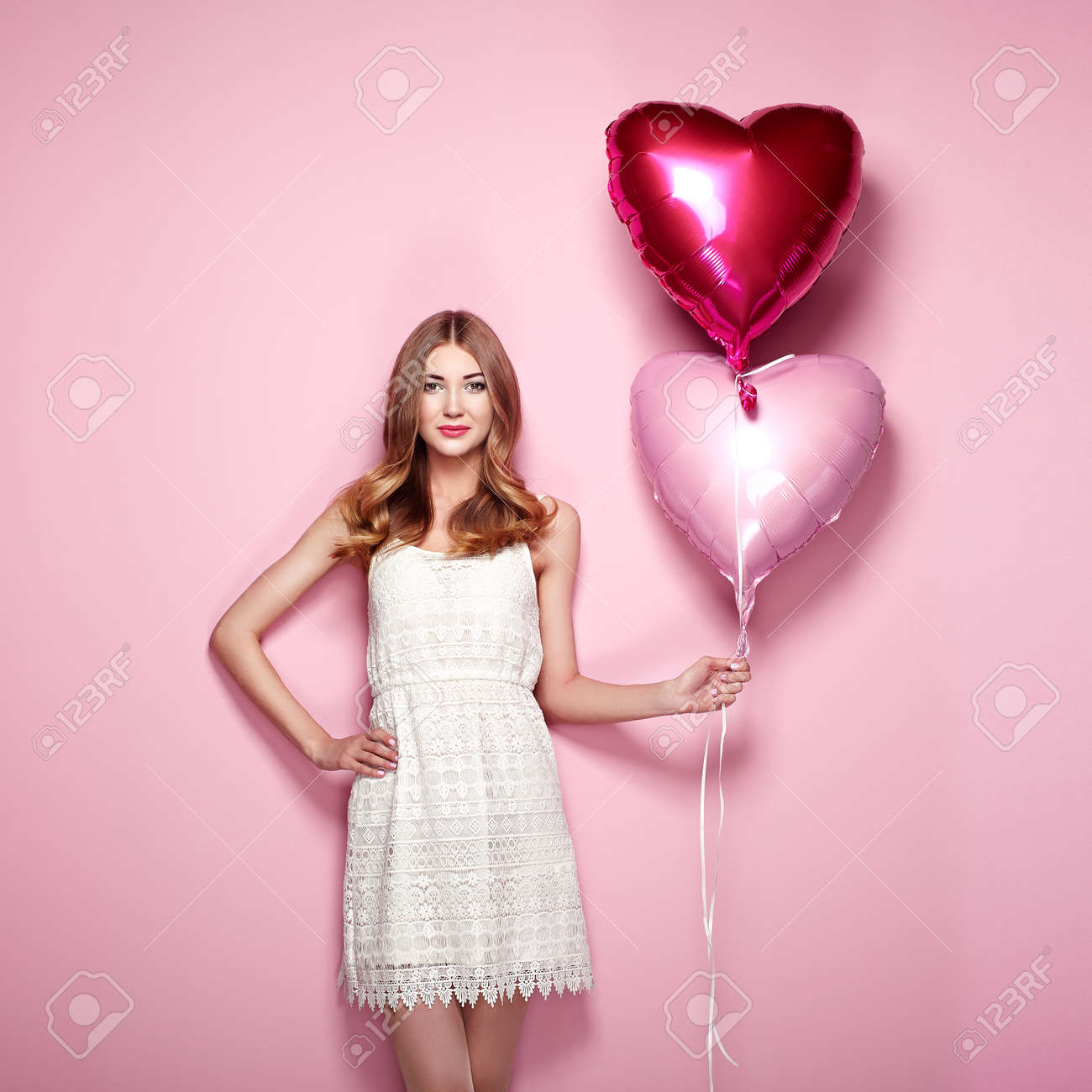 Beautiful young woman with heart shape air balloon on color background. Woman on Valentine's Day. Symbol of love - 70422942