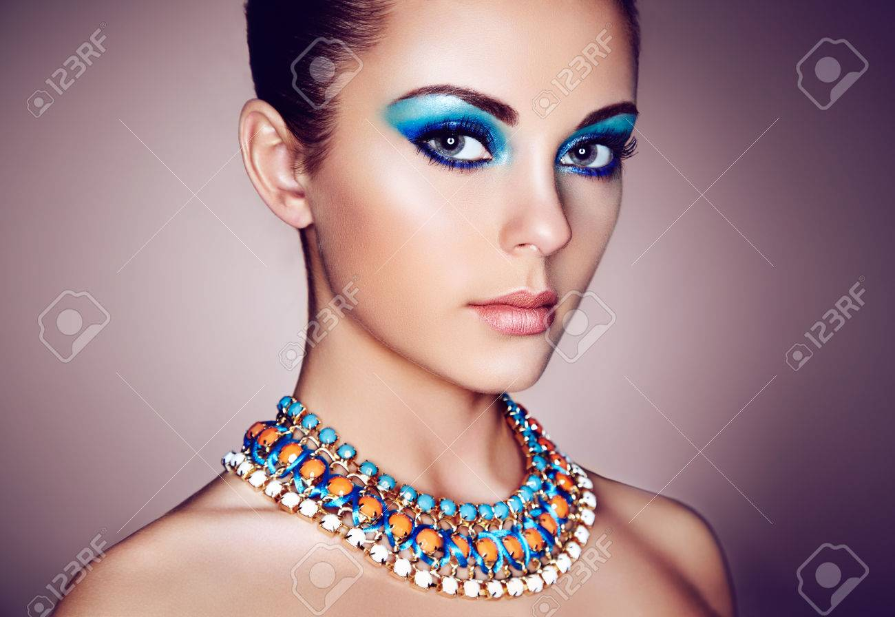 Portrait of young beautiful woman with blue makeup. Face Girl with necklace close up. Fashion jewelry - 70422950
