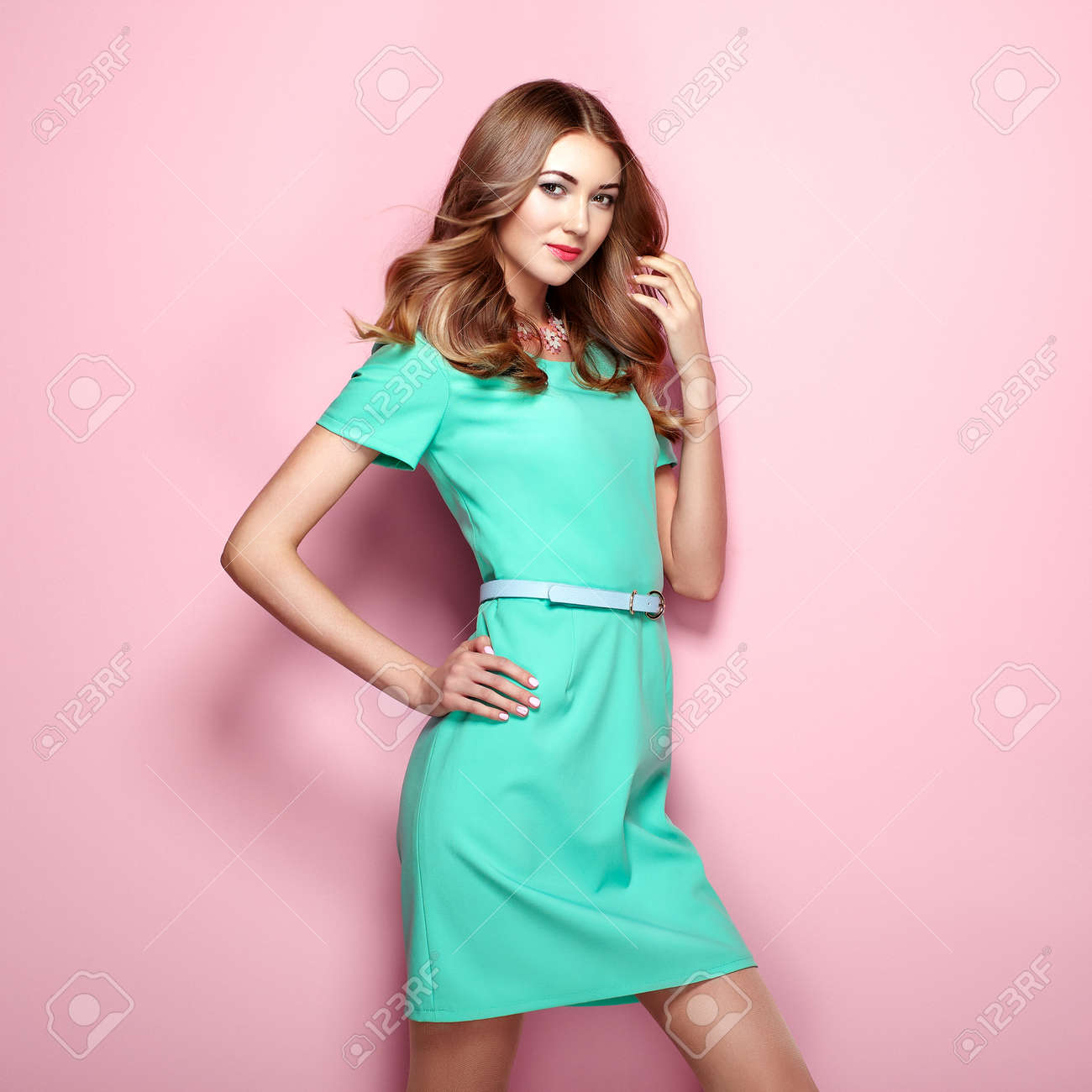 Blonde young woman in elegant green dress. Girl posing on a pink background. Jewelry and hairstyle. Fashion photo - 71386964