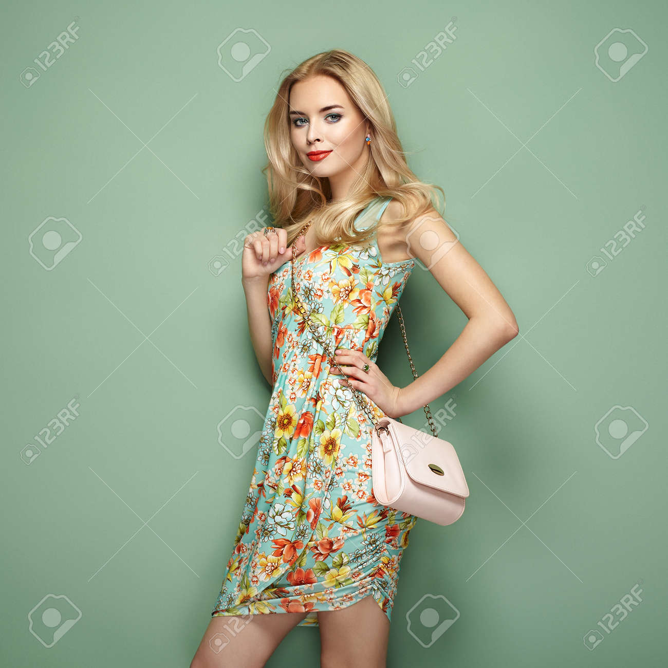 849c653ded Blonde young woman in floral summer dress. Girl posing on a green  background. Jewelry