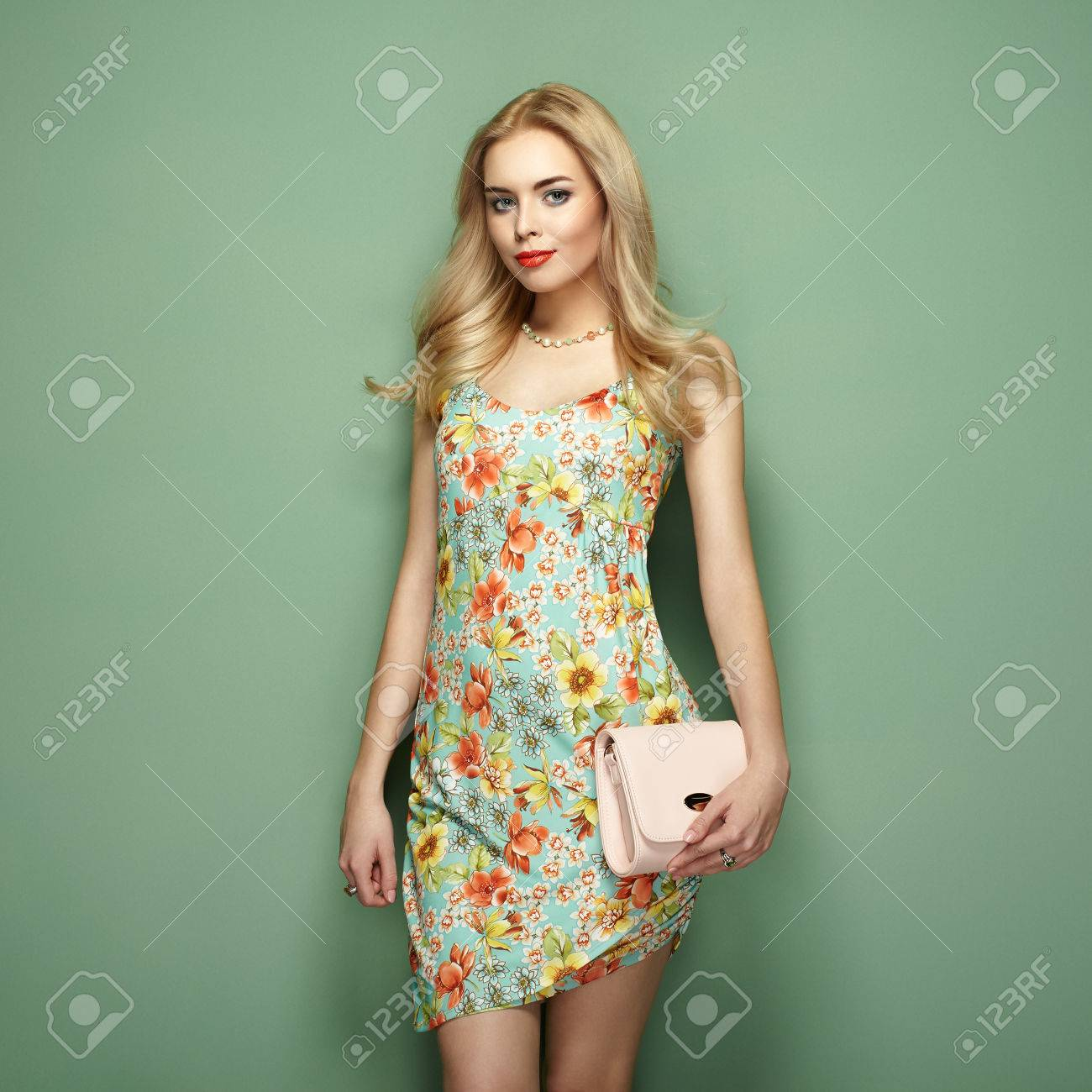 3c4d16666fc Blonde young woman in floral summer dress. Girl posing on a green background.  Jewelry