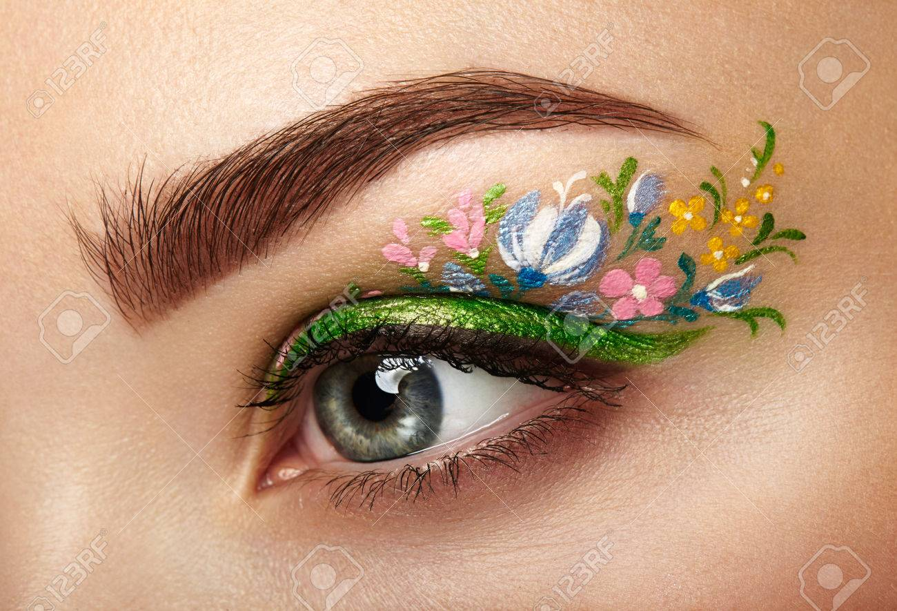 Eye makeup girl with a flowers. Spring makeup. Beauty fashion. Eyelashes. Cosmetic Eyeshadow. Make-up detail. Creative woman holiday make-up - 74276928
