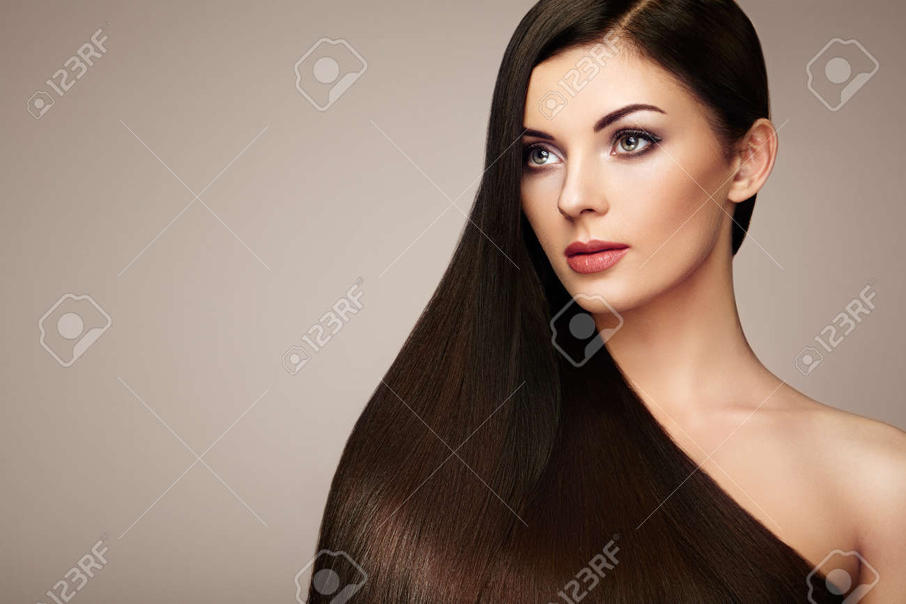 Beautiful woman with long smooth hair. Girl with perfect makeup and hairstyle. Model brunette with perfect healthy dark hair - 75527797