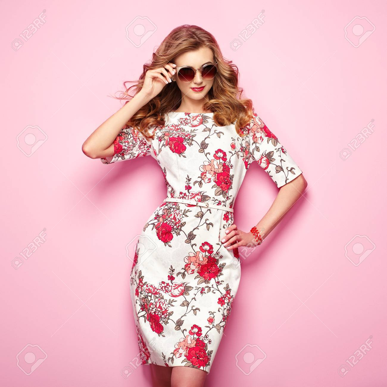Blonde young woman in floral spring summer dress. Girl posing on a pink background. Summer floral outfit. Stylish wavy hairstyle. Fashion photo. Glamour lady in stylish sunglasses - 75986989