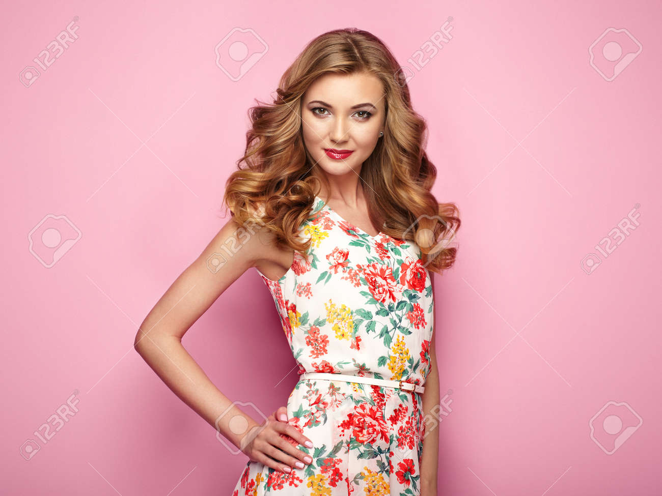 Blonde young woman in floral spring summer dress. Girl posing on a pink background. Summer floral outfit. Stylish wavy hairstyle. Fashion photo. Blonde lady - 76004080