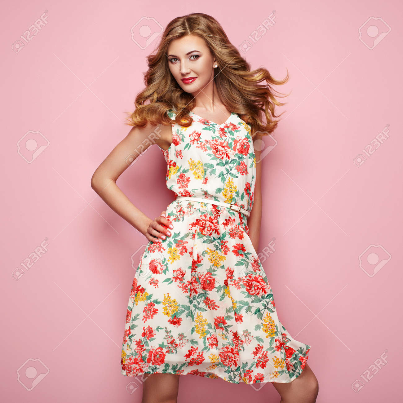 26ef244571c Blonde young woman in floral spring summer dress. Girl posing on a pink  background.