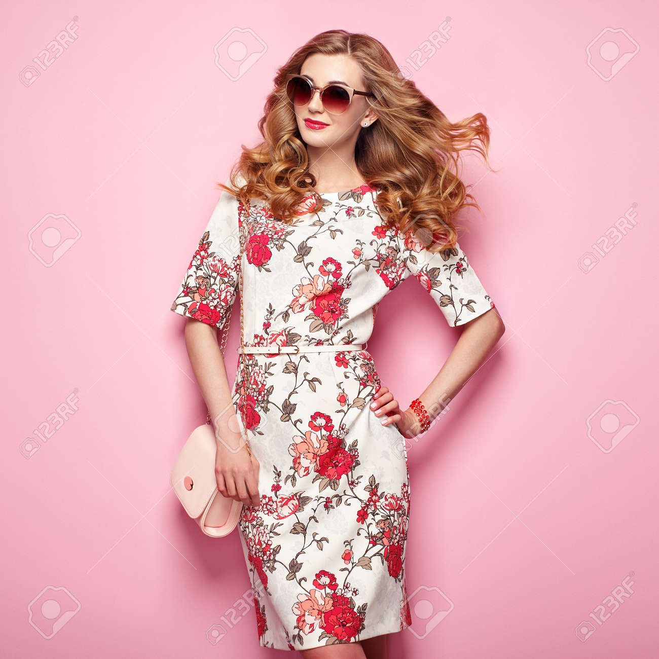 Blonde young woman in floral spring summer dress. Girl posing on a pink background. Summer floral outfit. Stylish wavy hairstyle. Fashion photo. Glamour lady in sunglasses with handbag - 76500420
