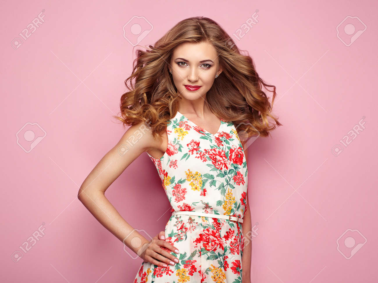 Blonde young woman in floral spring summer dress. Girl posing on a pink background. Summer floral outfit. Stylish wavy hairstyle. Fashion photo. Blonde lady - 76500417