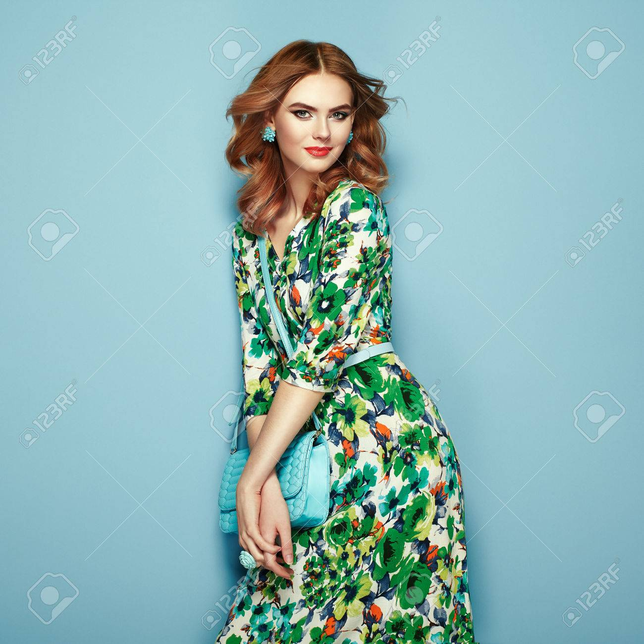 Blonde young woman in floral spring summer dress. Girl posing on a pink background. Summer floral outfit. Stylish wavy hairstyle. Fashion photo. Glamour lady with handbag - 77028787