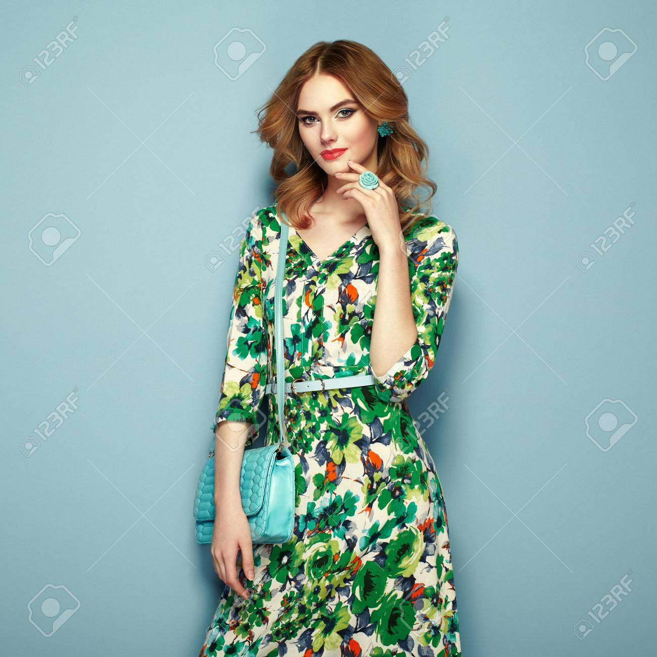 Blonde young woman in floral spring summer dress. Girl posing on a pink background. Summer floral outfit. Stylish wavy hairstyle. Fashion photo. Glamour lady with handbag - 77028798