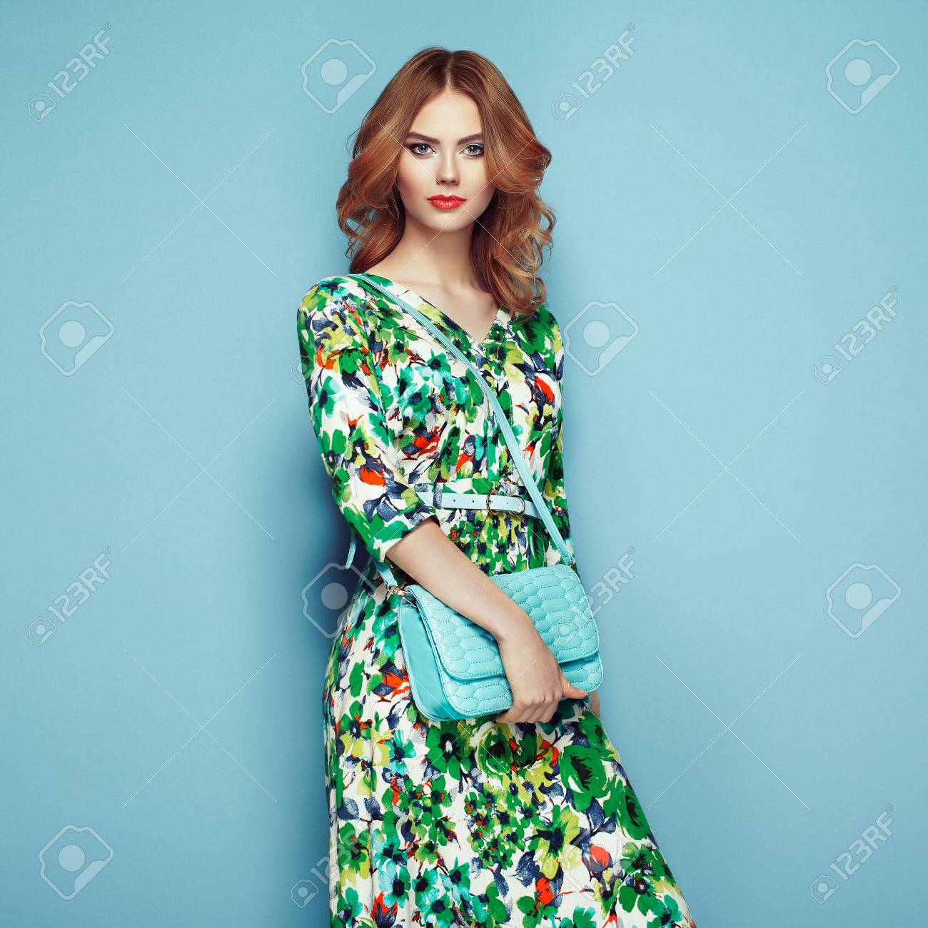 Blonde young woman in floral spring summer dress. Girl posing on a pink background. Summer floral outfit. Stylish wavy hairstyle. Fashion photo. Glamour lady with handbag - 77028799