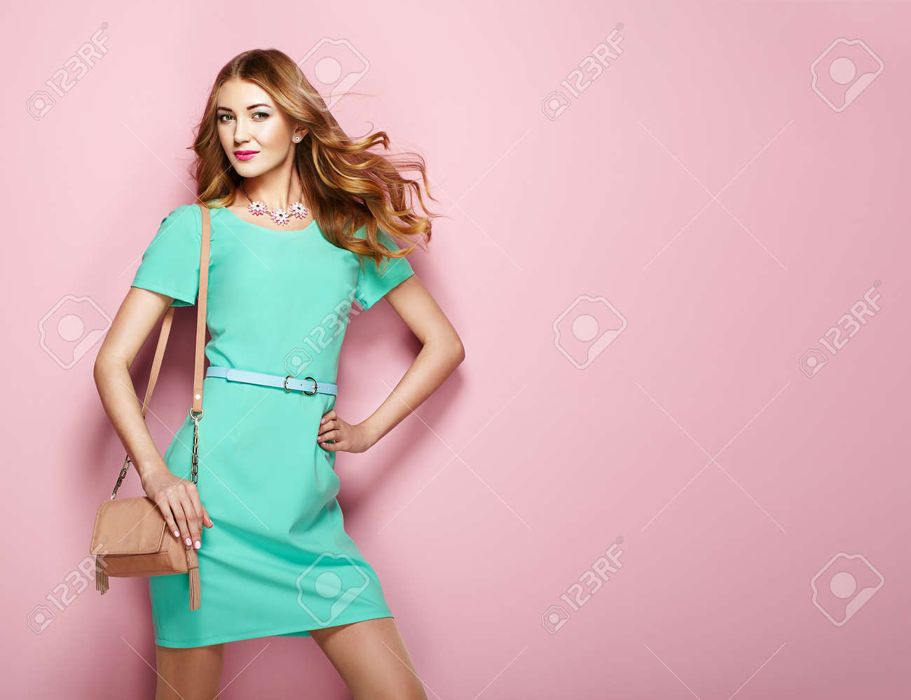 df1f0301928 Blonde young woman in elegant green dress. Girl posing on a pink background.  Jewelry