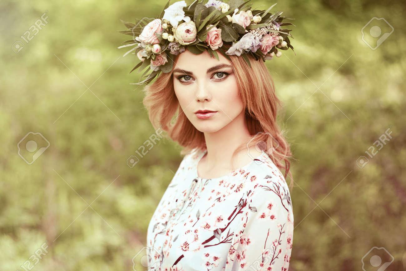Schöne blonde Frau mit Blumenkranz auf dem Kopf. Schönheit Mädchen mit  Blumen Frisur. Mädchen in einem Sommer Wald. Mode-Foto