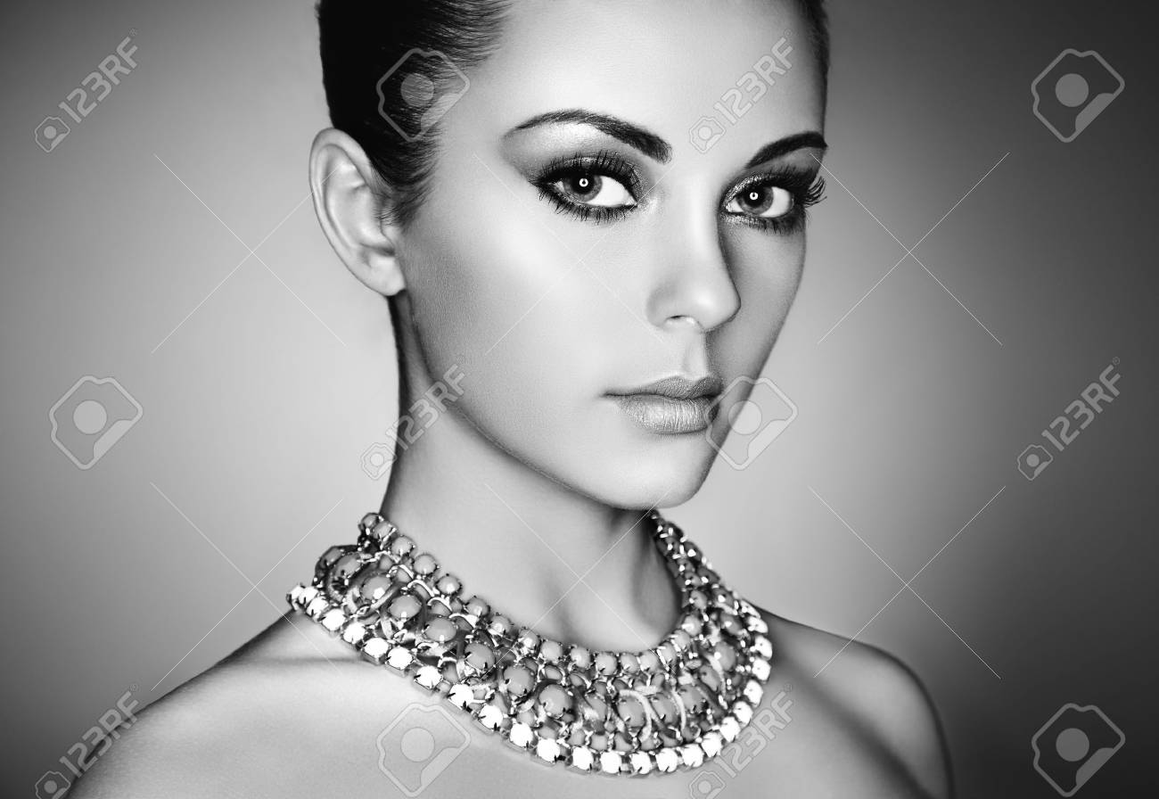 Portrait of young beautiful woman with perfect makeup. Face Girl with necklace close up. Fashion jewelry. Black and White photo - 81163834