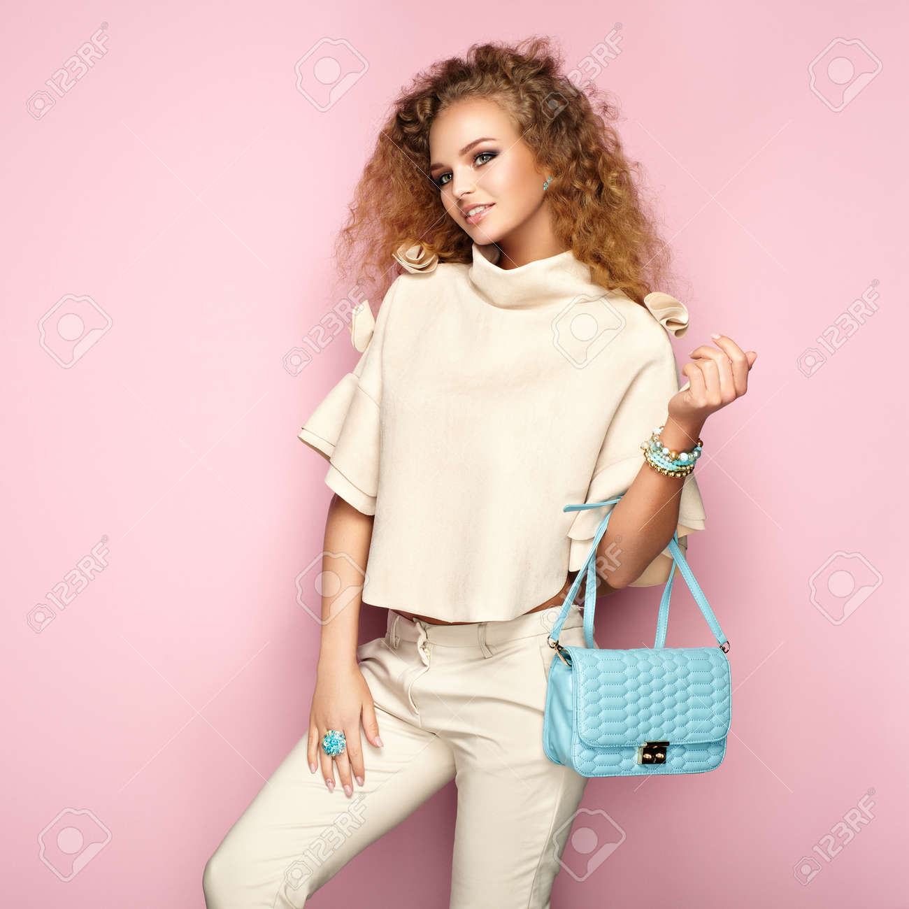 Fashion portrait of woman in summer outfit. Girl posing on pink background. Blue handbag. Stylish curly hairstyle. Glamour lady - 82310064