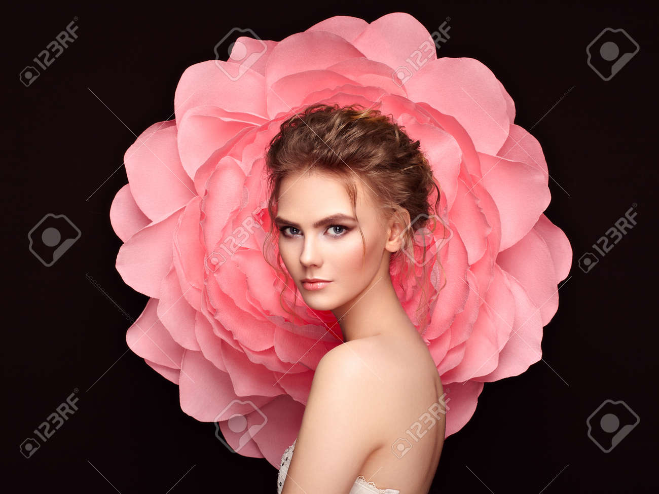 Beautiful woman on the background of a large flower. Beauty summer model girl with pink peony. Young woman with elegant hairstyle and makeup. Fashion photo - 84923132