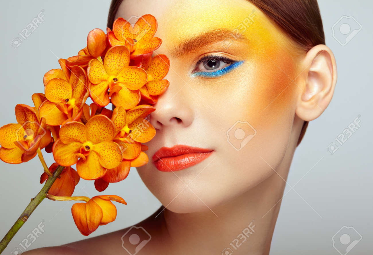 Portrait of beautiful young woman with orchid. Brunette woman with luxury makeup. Perfect skin. Eyelashes. Cosmetic eyeshadow. Orange flowers - 84923141