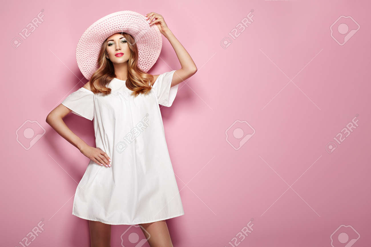 Blonde Young Woman in elegant white Dress and Summer Hat. Girl posing on a Pink Background. Jewelry and Clothing. Fashion photo - 88181466