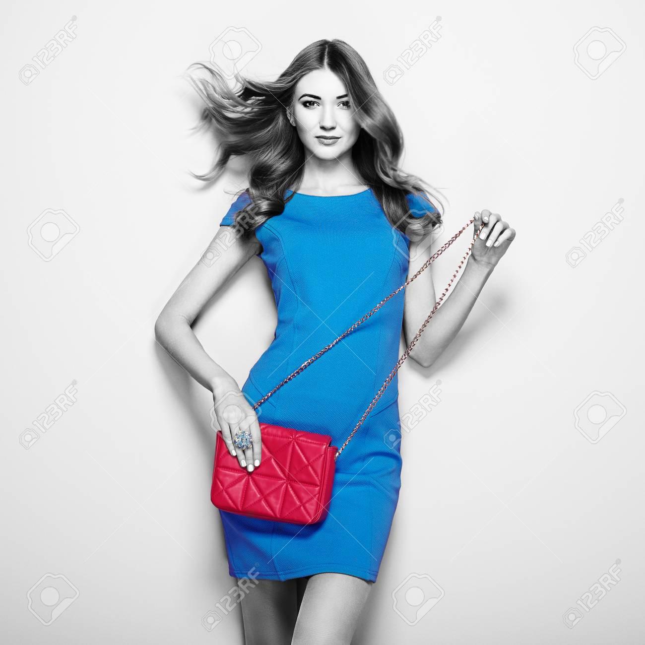 huge discount 84770 05e4a Giovane donna castana in vestito blu elegante. Ragazza che propone su una  priorità bassa bianca. Gioielli e acconciatura. Ragazza con la borsetta ...