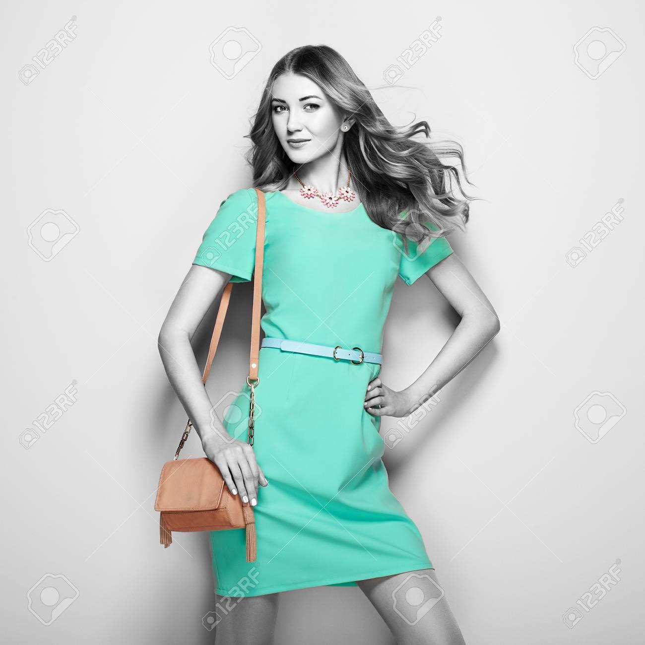 premium selection 368cd 61a43 Giovane donna bionda in abito verde elegante. Ragazza che propone su una  priorità bassa bianca. Gioielli e acconciatura. Ragazza con borsetta Foto  di ...