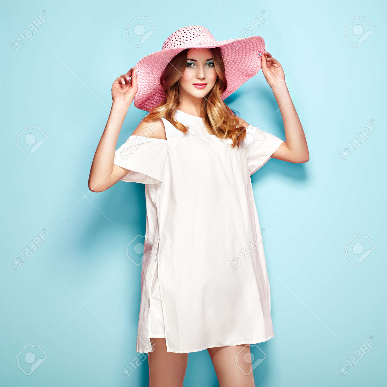 new arrival 45dd4 b8bfe Giovane donna bionda in estate vestito bianco e cappello estivo. Ragazza  che propone su una priorità bassa del turchese. Acconciatura e  abbigliamento. ...