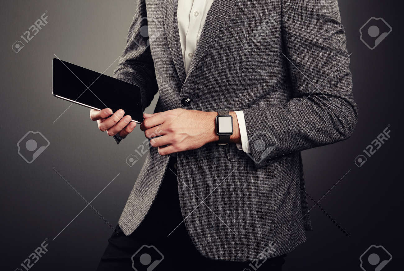 b90c626e20b Handsome Young Man in Business Suit. Casual style and Electronic Gadgets.  Smart Watches and