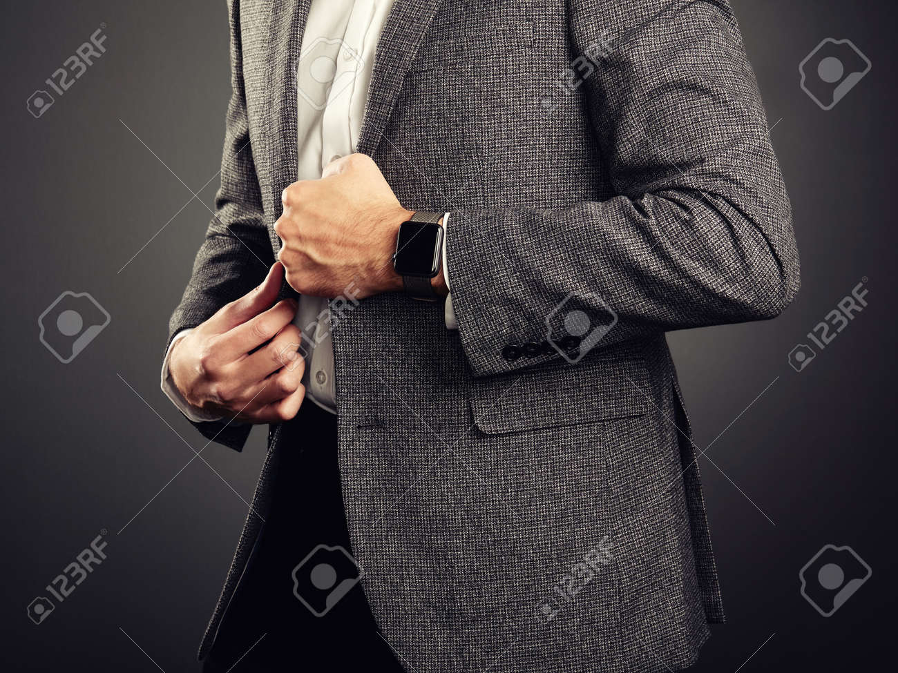 89068deea72 Handsome Young Man in Business Suit. Casual Style and Electronic Gadgets.  Smart Watch
