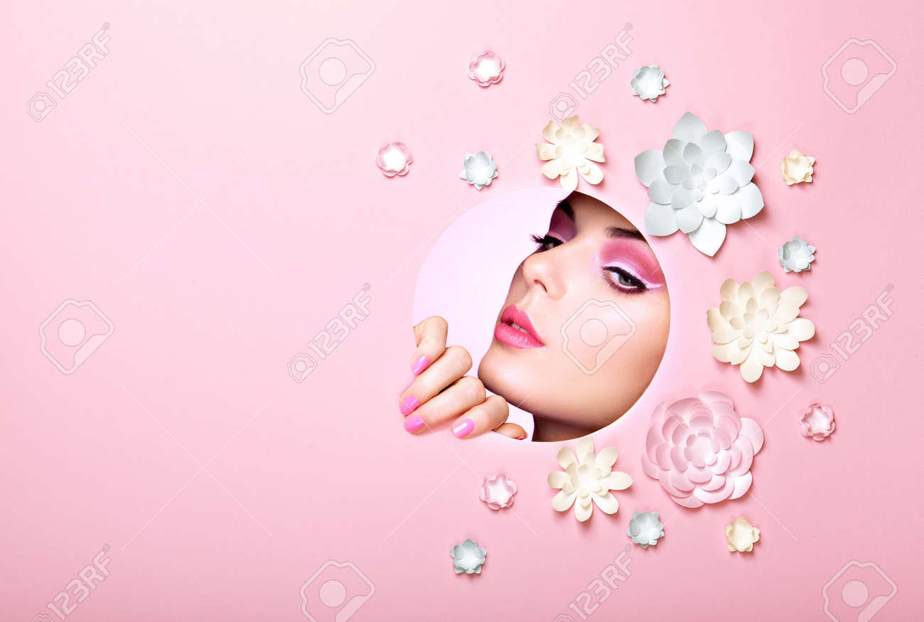 Conceptual Beauty Portrait of Beautiful Young Woman. Face of Girl with Spring Pink Make-up. Beauty Fashion Model Woman Face perfect Skin. Paper Flowers on Pink Background - 93516231