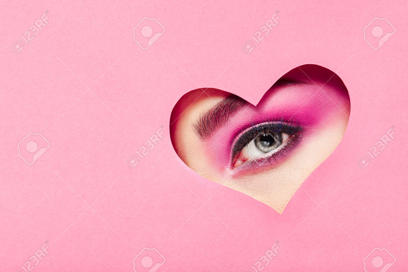 Conceptual photo of Valentine's day. Eye of Girl with Festive Pink Makeup. Paper heart on a pink background. Love symbols Valentines day - 94919549