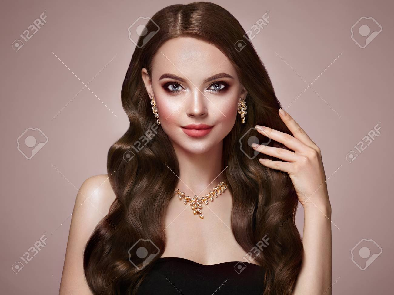 Brunette Girl with Long Healthy and Shiny Curly Hair. Care and Beauty. Beautiful Model Woman with Wavy Hairstyle. Make-Up and Jewelry - 103367398