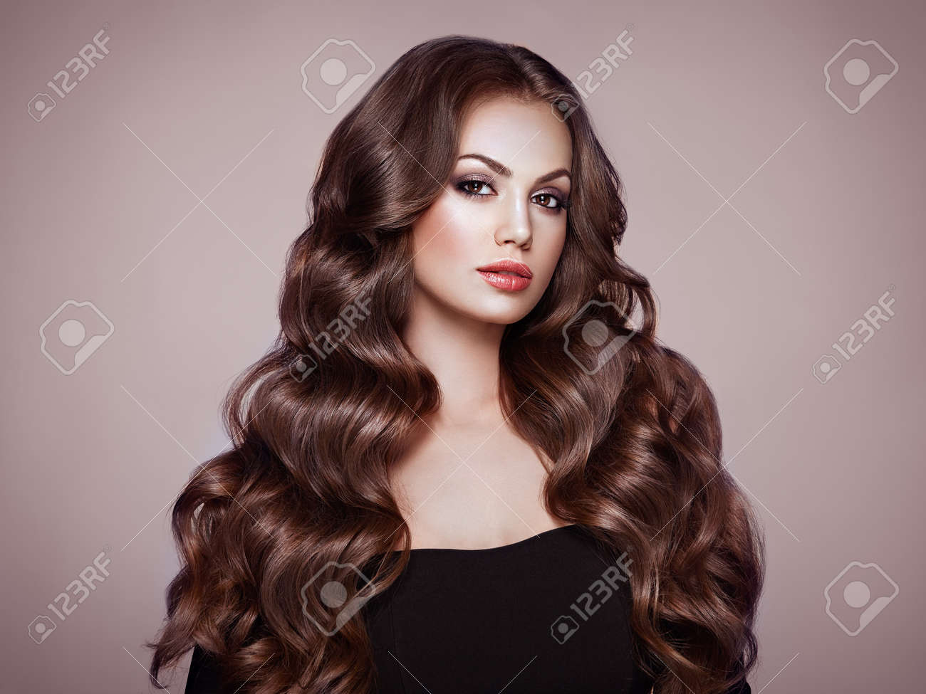 Brunette Girl with Long Healthy and Shiny Curly Hair. Care and Beauty. Beautiful Model Woman with Wavy Hairstyle. Make-Up and Black Dress - 112453340
