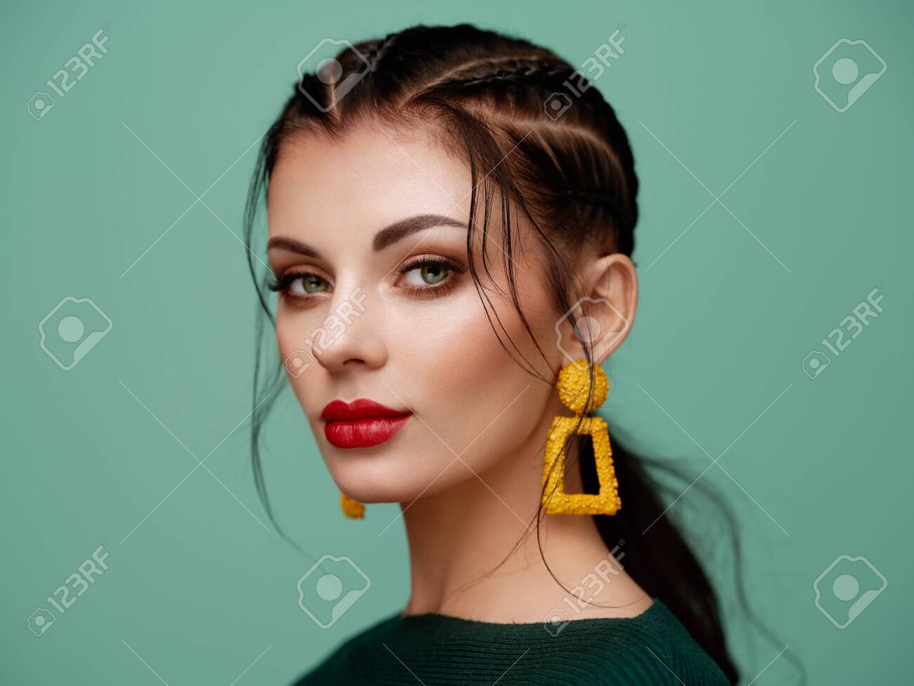 Brunette girl with perfect makeup. Beautiful model woman with curly hairstyle. Care and beauty hair products. Lady with braided hair. Model with jewelry. Turquoise background - 125293691
