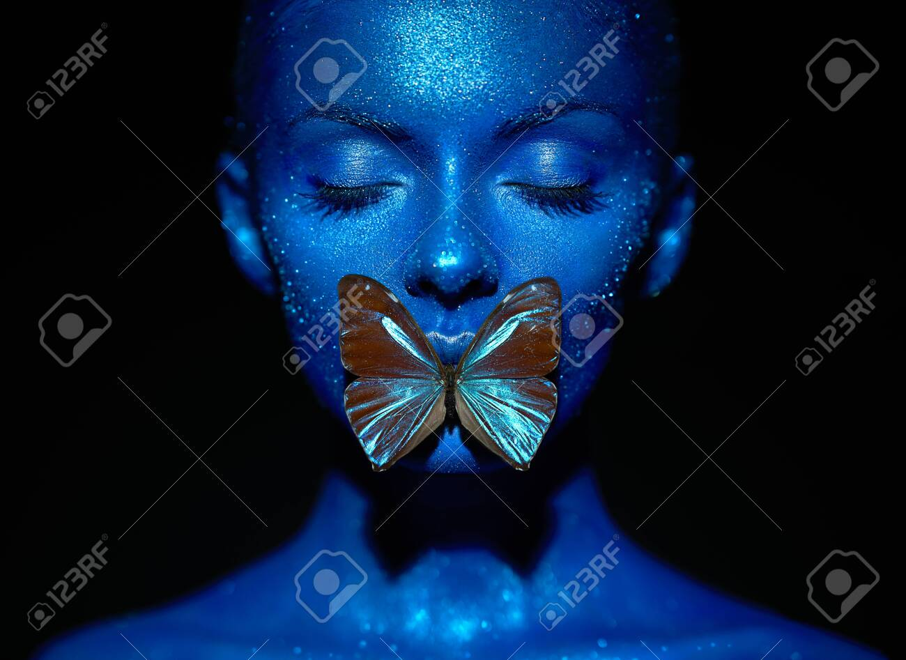 Fashion model woman in blue bright sparkles and neon lights posing in studio. Portrait of beautiful woman with blue butterfly. Art design colorful glitter glowing make up - 127785142