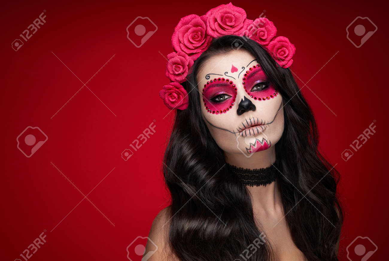 Portrait of a woman with sugar skull makeup over red background. Halloween costume and make-up. Portrait of Calavera Catrina - 130723605