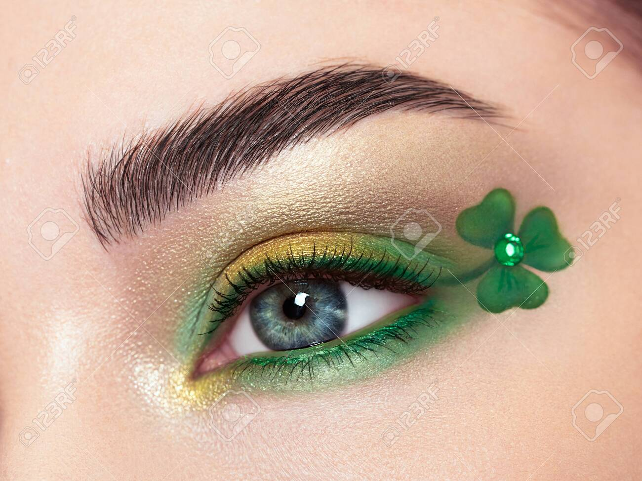 Conceptual photo of St. Patrick's Day. The eye of the young beautiful woman with bright green shadows and expressive eyebrows. Shamrock patterns. Holiday makeup - 140982411