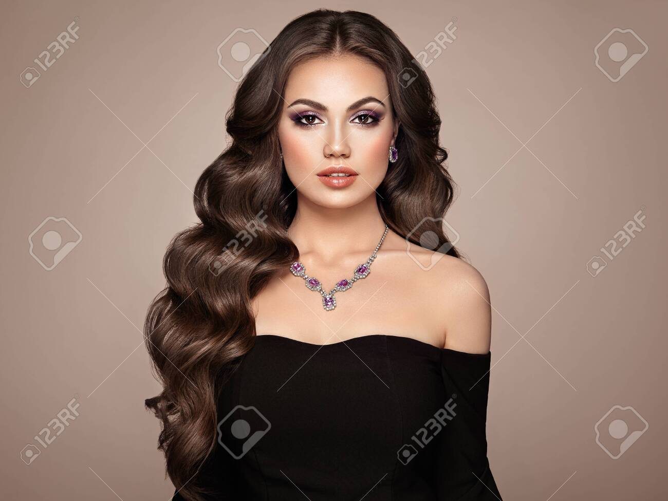 Brunette Girl with Long Healthy and Shiny Curly Hair. Care and Beauty. Beautiful Model Woman with Wavy Hairstyle. MakeUp and Jewelry - 152655326