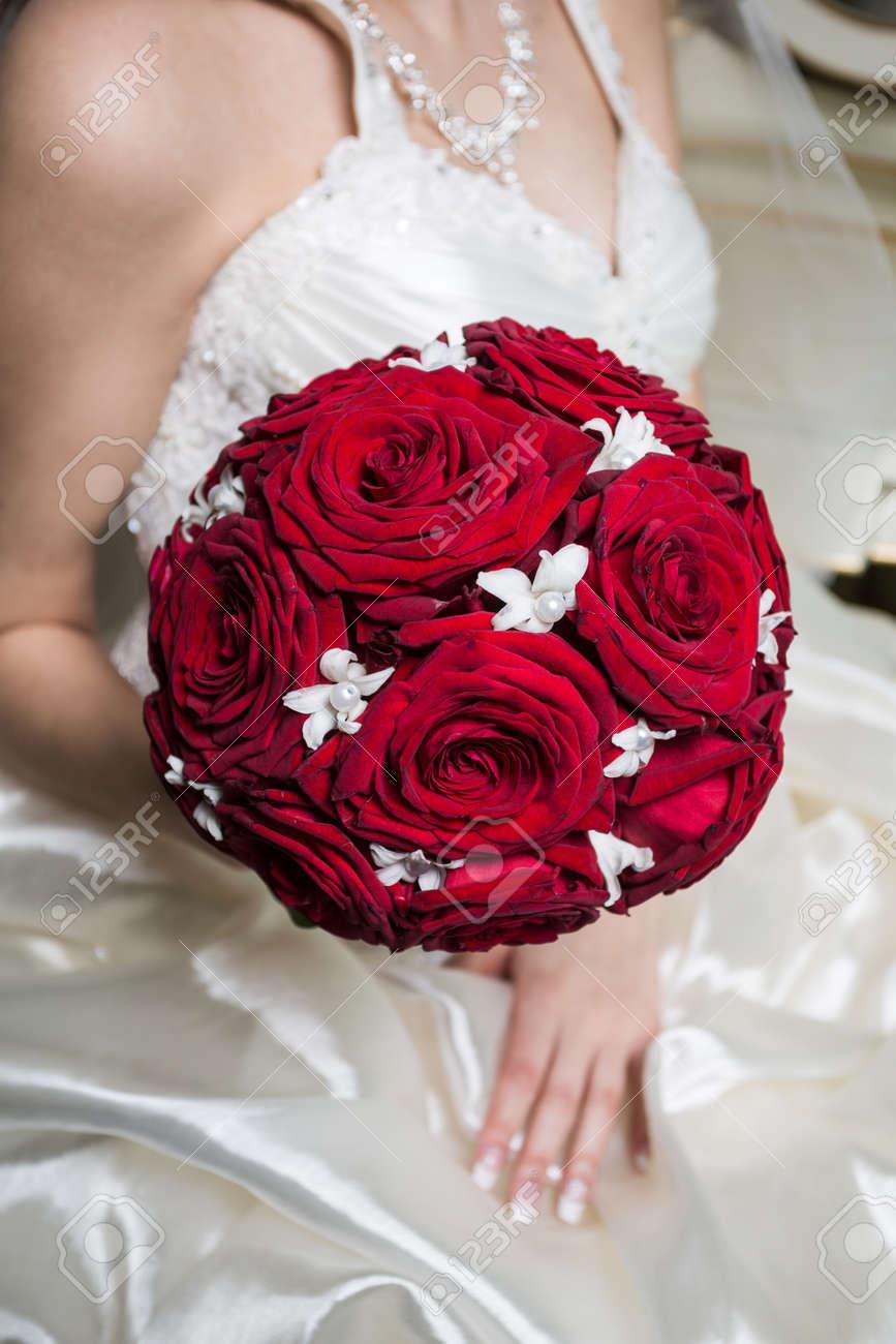 Foto de archivo , Primer plano de una novia con un ramo de la boda con rosas rojas