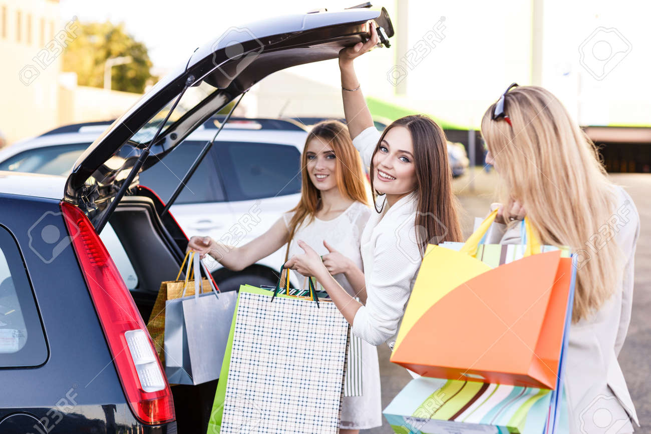 Group Of Girls After Shopping Loading A Shopping Bags In A Car ...